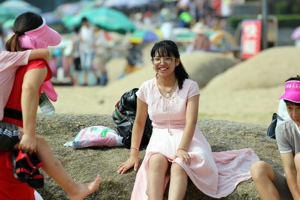 旅游者选择一早一晚出动,到海水浴场享受大海的丝丝清凉。