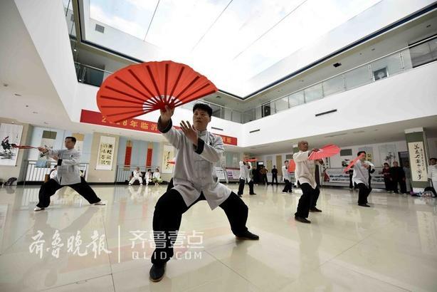 """临沂市太极拳""""准教官""""在教练的指导下练习太极扇。"""