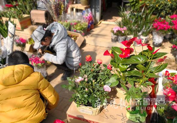 一位摊主正在打理花卉。