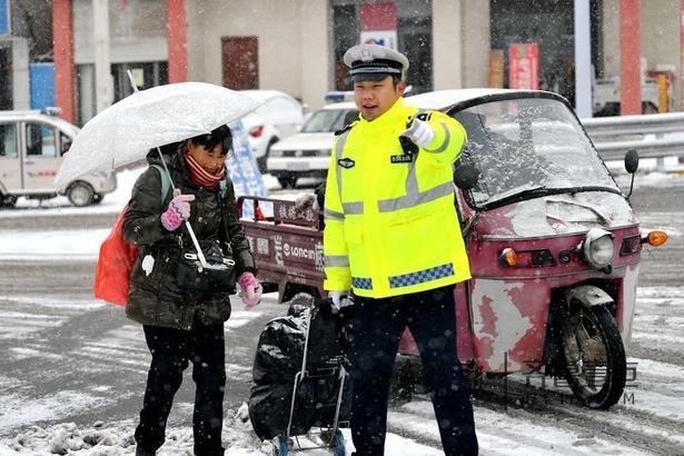 图为执勤民警帮助出行群众拿行李,确保群众安全过马路。