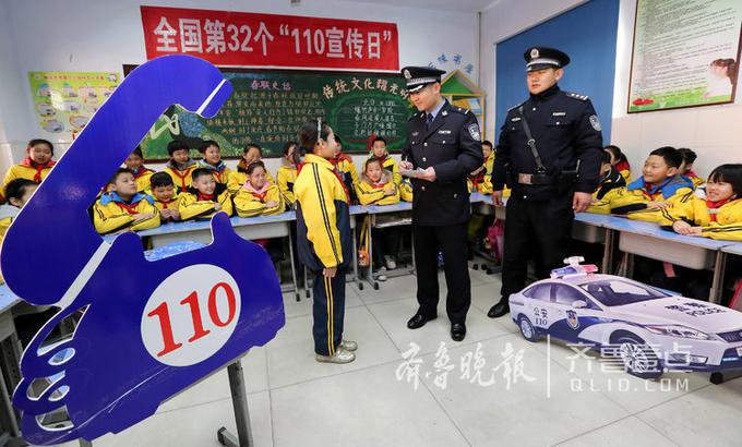 """2018年1月10日是全国第32个""""110宣传日""""。9日,枣庄市公安局市中分局组织民警深入辖区中小学开展""""110宣传进校园""""活动,把110历史的由来、服务内容、拨打方法等编成""""情景剧""""以及与学生们一起做趣味游戏等形式,让学生们在享受快乐的同时了解110常识,帮助他们学会正确运用110保护自身安全。图为1月9日,民警在光明路小学向学生表演自编的""""110情景剧""""。"""