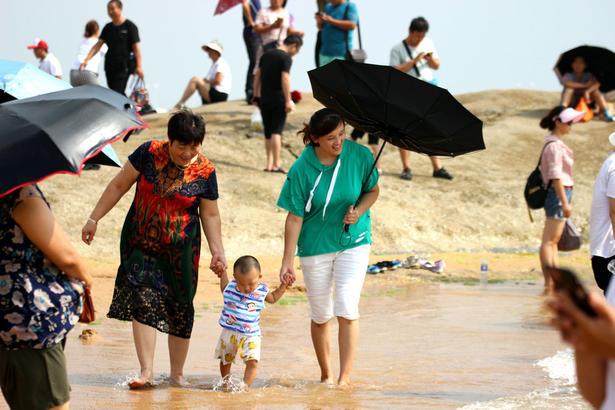 孩子们赤裸裸地尽情在海水中嬉戏,牵着大人的手在海水边学步,在沙滩上堆沙玩耍。