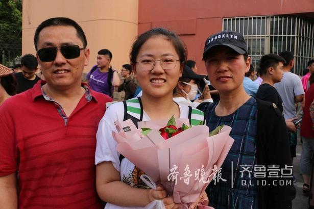 还有些家长和学生纷纷在校门口与家长合影留念,也有部分家长为孩子送来鲜花表示庆祝。