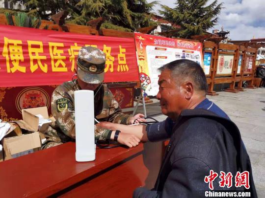 图为3月14日,游客在拉萨大昭寺门前的便民医疗服务点前问诊。 张伟 摄