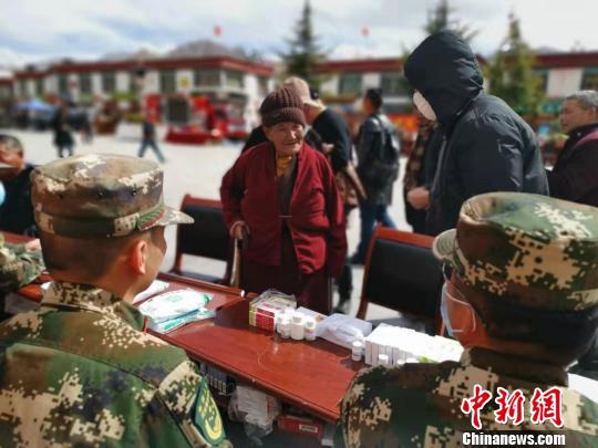 图为3月14日,一位藏族老阿妈在拉萨大昭寺门前的便民医疗服务点前问诊。 张伟 摄