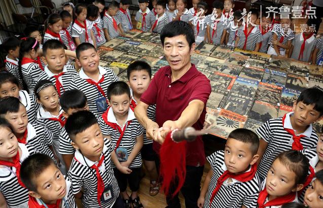 9月3日,在枣庄市红旗小学,校外辅导员、民间收藏爱好者杨义平(中)在向学生们展示当地抗日英雄与侵华日军搏斗时使用的红缨枪。