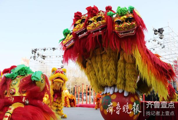 """2018年12月31日,在京杭大运河畔的枣庄台儿庄古城,民间艺人在向游客表演""""狮子滚绣球""""。"""