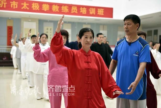 """临沂市体协太极拳教练李西华(左一)在指导""""准教官""""练习太极拳。"""