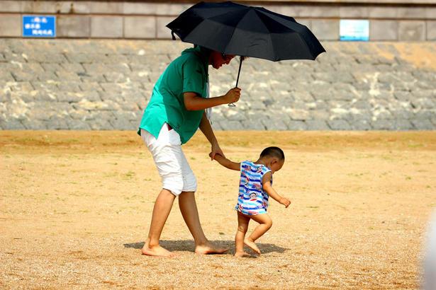 牵着大人的手,在海滩上学步。