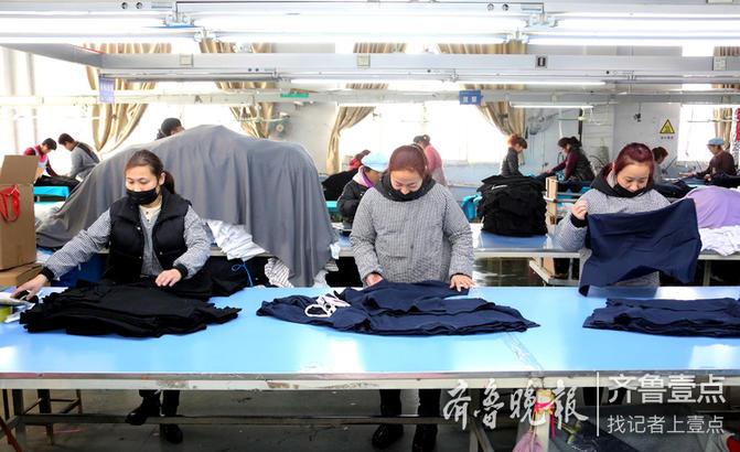2月11日,枣庄市一家纺织公司的工人在车间生产出口服装。 摄影:吉 喆