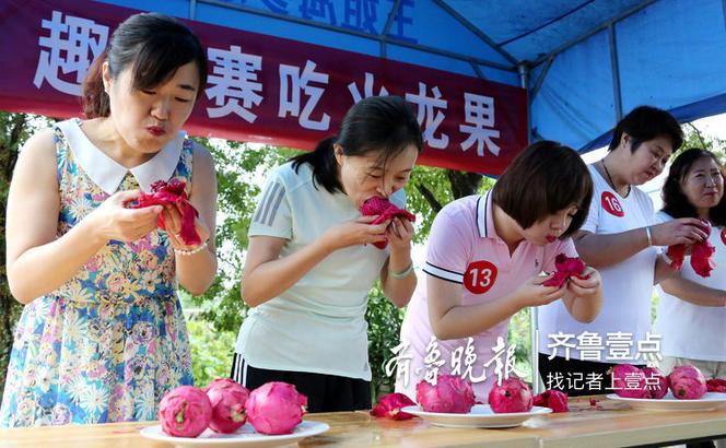7月29日,参赛者在枣庄市永安镇蔡庄村安邦家庭农场参加女子组吃火龙果趣味比赛。