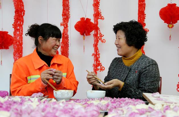 图为:11月7日,枣庄市光明路街道陈庄社区,老党员周保萍(右)和环卫工人曹利一起包饺子、唠家常。