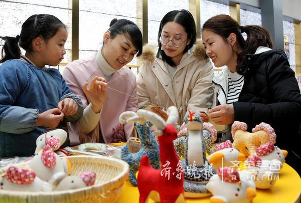 图为2月8日,民间艺人唐慧(左二)在向市民免费传授手工布艺的制作技艺。