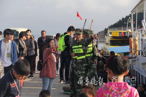 """这时候也是边防官兵最忙的时候,他们每天都会安排人员到码头执勤,引导游客有序上 下船、乘车,执勤时间往往会超过10个小时,王磊说:""""很多游客都是第一次上岛,我们累点没关系,咱们必须得保证游客的安全。"""""""