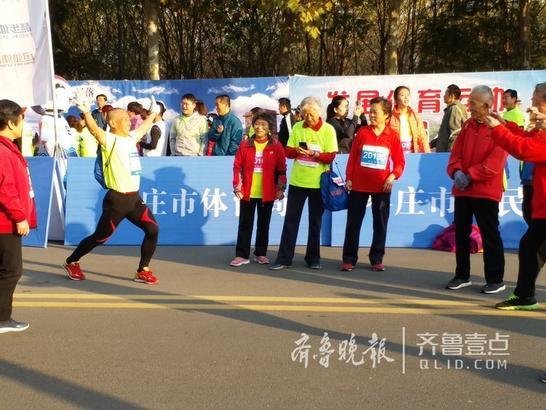 """11月12日,""""跑游山东""""枣庄国际马拉松赛在新城文体中心鸣枪开跑,开跑之前,一群银发老人特别引人注意,他们用实际行动诠释生命在于运动。齐鲁晚报·齐鲁壹点记者 杨蕾 摄影报道"""