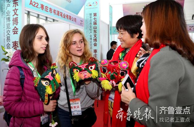 """民间艺人在向来自俄罗斯的姑娘莉卡(左一)、安娜(左二)介绍枣庄市级非遗项目""""运河莲花锦帽""""的制作技艺。"""