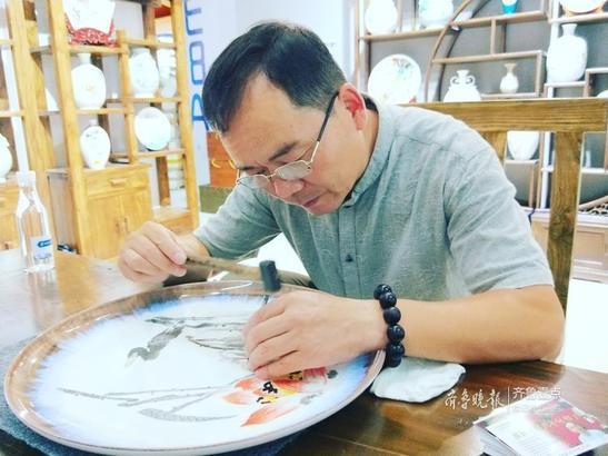 国家级大师张新中正在进行刻瓷表演,作品名为《荷塘清趣》。