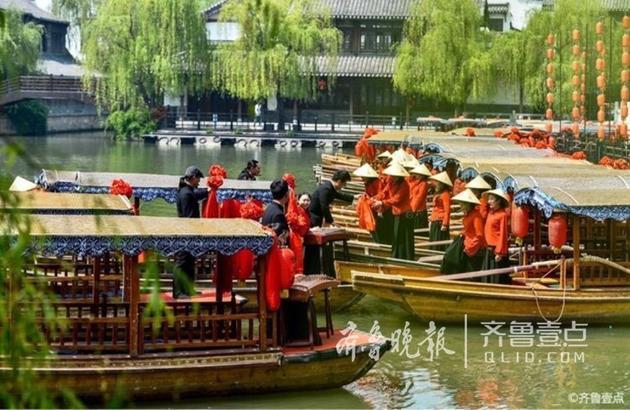 """18日,壹粉""""天下看台""""情报站发帖称,台儿庄古城景区的员工们身着盛装在古运河上向游客表演情歌对唱"""