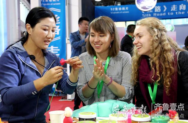 """来自济南的国家级非遗项目""""汤派""""面塑第三代传承人王丽丽(左一)在向外国友人传授面塑制作技艺。"""