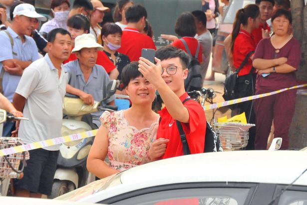 在枣庄市第一中学考场外,考生在和家长自拍。