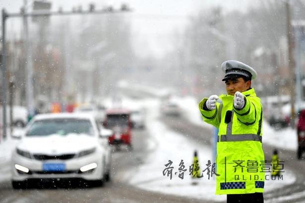 图为民警在雪中执勤,确保车辆、行人安全通行。