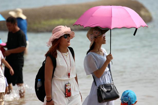 大人们则把自己的上身裹得严严实实,赤脚泡在海水里,欣赏海景,忙着自拍,其乐融融。