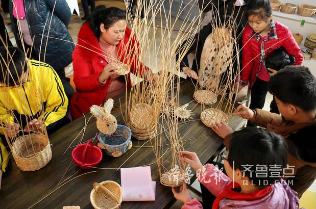 图为2月8日,民间艺人张亚亚(左二)在现场免费向人们传授柳编技术。