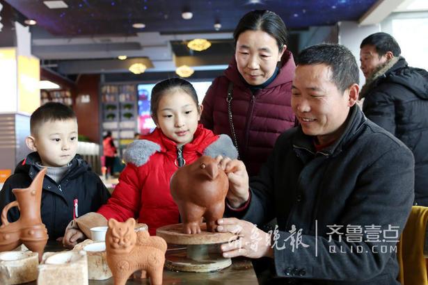 """图为2月8日,""""伏里土陶""""传承人甘言地(右二)现场向观众展示伏里土陶的制作技艺。"""