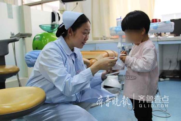 """儿童口腔 张玉静 摄 """"宝贝,你真勇敢,阿姨颁给你'勇敢奖章'!"""" 治疗结束了,因为宝宝今天表现出色,护士阿姨为宝宝颁发奖励——小贴画,贴画上面是牙齿保健的一些知识。护士说:""""要预防龋齿!"""" """"要预防龋齿""""孩子跟着咿呀学语。"""