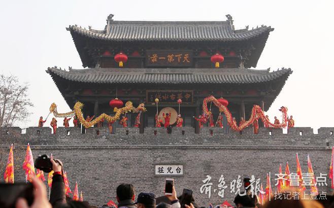 2019年1月1日,在京杭大运河畔的枣庄台儿庄古城,民间艺人在古城楼上进行舞龙表演。