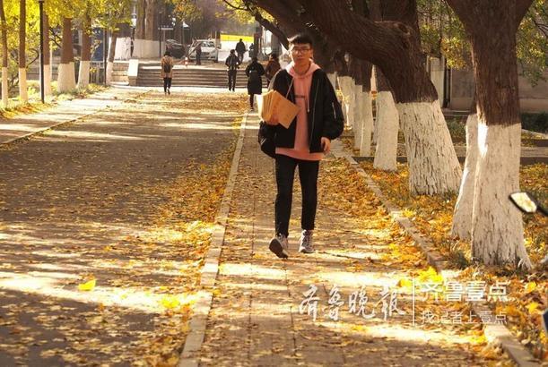 9日,山东师大千佛山校区,师生们踏着金色落叶行走在校园内,不时有人留步摄影留念。
