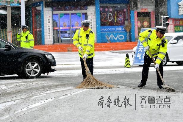 图为执勤民警清扫路面积雪,确保车辆、行人安全通行。