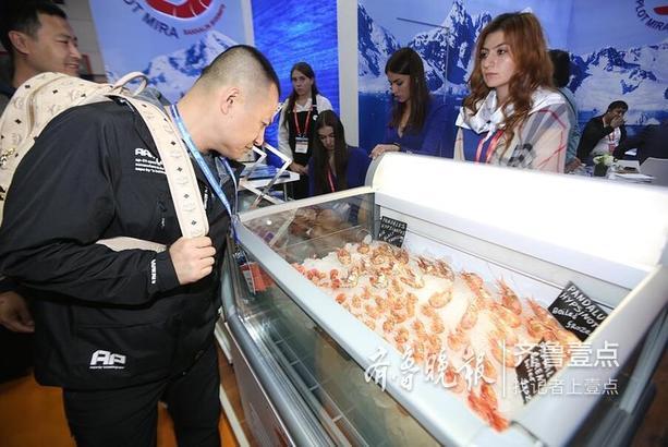 来自俄罗斯展团的工作人员客商介绍深海鱼展品。此次他们从俄罗斯携带了大尺寸、味道鲜美的各类螃蟹、贝壳、深海鳕鱼等上百种海产品来参展,均为来自海洋2500米以下的深海鱼,同时会安排各个展商在现场新鲜烹制俄罗斯渔产品,前来参观的客户可以在现场免费品尝试吃。